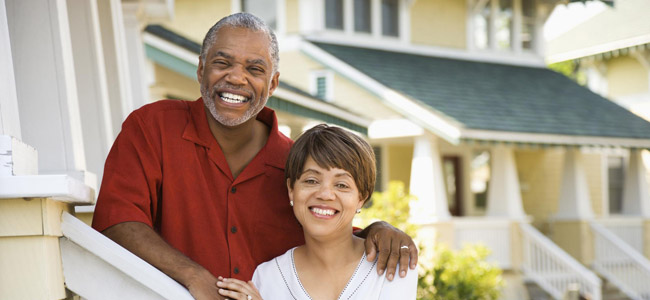 Tooth Extractions - Danbury, CT & Brookfield, CT - Couple smiling on front steps of their home