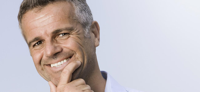 Mature gentleman grinning after receiving painless root canal therapy at Soams Dental Care